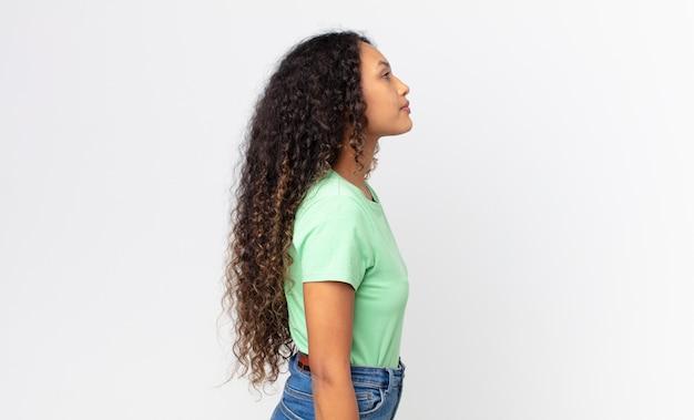 Ładna latynoska kobieta w widoku profilu, która chce skopiować przestrzeń do przodu, myśląc, wyobrażając sobie lub marząc na jawie