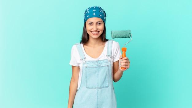 Ładna latynoska kobieta wygląda na szczęśliwą i mile zaskoczoną. koncepcja malowania domu