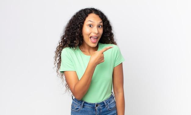 Ładna latynoska kobieta wyglądająca na podekscytowaną i zaskoczoną, wskazując na bok i w górę, aby skopiować przestrzeń