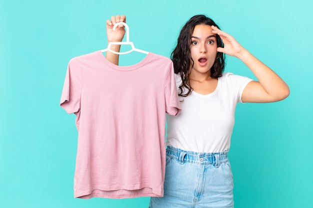Ładna latynoska kobieta wyglądająca na szczęśliwą, zdumioną i zdziwioną wybierając ubranie