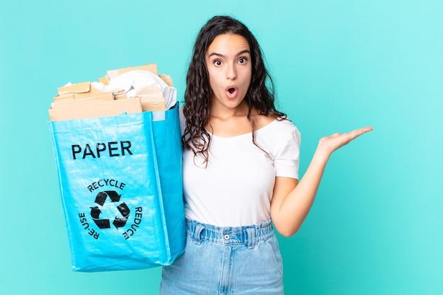 Ładna latynoska kobieta wyglądająca na zaskoczoną i zszokowaną, z opuszczoną szczęką, trzymająca przedmiot i trzymającą papierową torbę z recyklingu