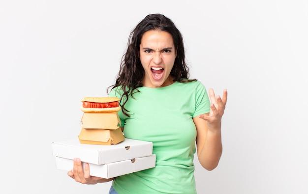 Ładna latynoska kobieta wyglądająca na złą, zirytowaną i sfrustrowaną, trzymającą na wynos pudełka z fast foodami