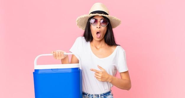 Ładna latynoska kobieta wyglądająca na zszokowaną i zaskoczoną z szeroko otwartymi ustami, wskazującą na siebie przenośną lodówką na piknik