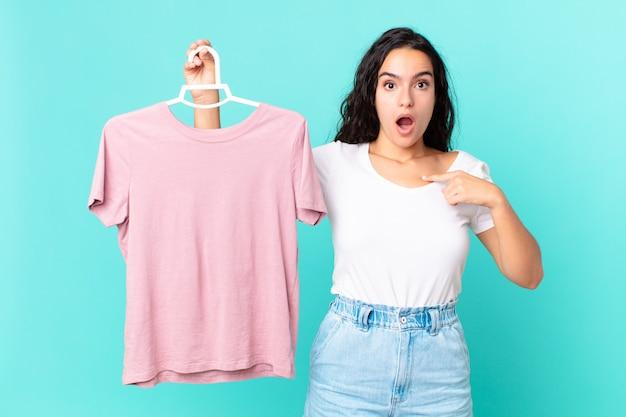 Ładna latynoska kobieta wyglądająca na zszokowaną i zaskoczoną z szeroko otwartymi ustami, wskazującą na to, że sama wybiera ubranie