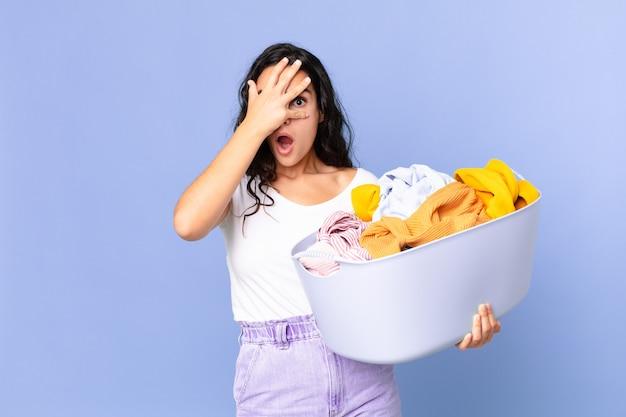 Ładna latynoska kobieta wyglądająca na zszokowaną, przestraszoną lub przerażoną, zakrywająca twarz dłonią i trzymająca kosz na pranie