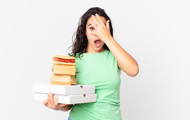 Ładna latynoska kobieta wyglądająca na zszokowaną, przestraszoną lub przerażoną, zakrywająca twarz dłonią i trzymająca na wynos pudełka z fast foodami