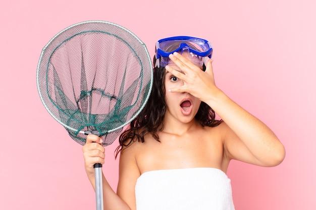 Ładna latynoska kobieta wyglądająca na zszokowaną, przestraszoną lub przerażoną, zakrywającą twarz ręką z goglami i siecią rybacką
