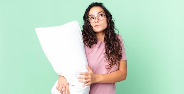 Ładna latynoska kobieta wzrusza ramionami, czuje się zdezorientowana i niepewna, ma na sobie piżamę z poduszką