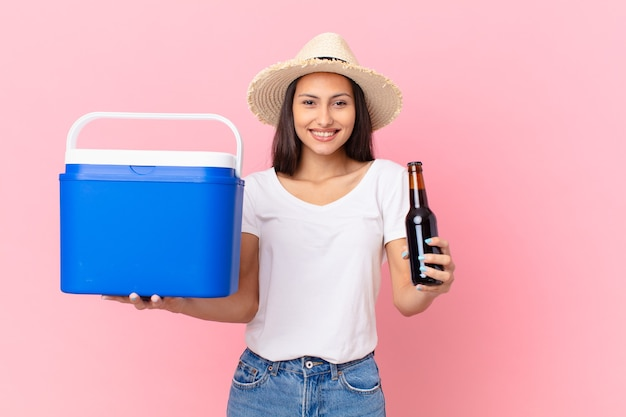 Ładna latynoska kobieta z przenośną zamrażarką i piwem