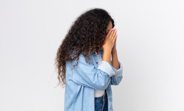 Ładna latynoska kobieta zakrywająca oczy dłońmi ze smutnym, sfrustrowanym wyrazem rozpaczy, płaczu, widoku z boku