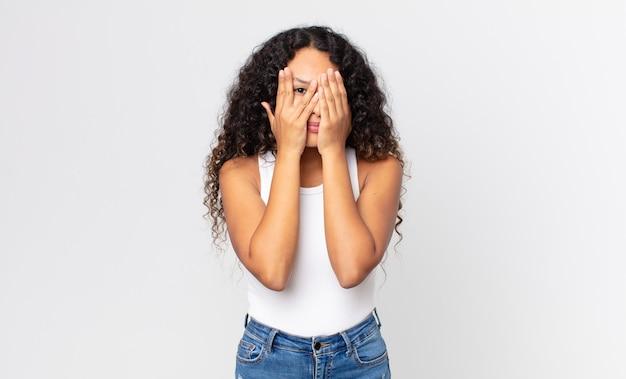 Ładna latynoska kobieta zakrywająca twarz dłońmi, zerkająca między palcami ze zdziwionym wyrazem twarzy i patrząca w bok
