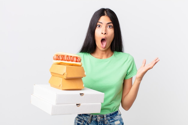 Ładna latynoska kobieta zdumiona, zszokowana i zdumiona niewiarygodną niespodzianką i trzymającą na wynos pudełka z fast foodami