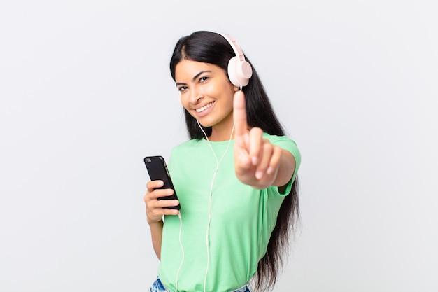 Ładna latynoska kobieta ze słuchawkami i smartfonem