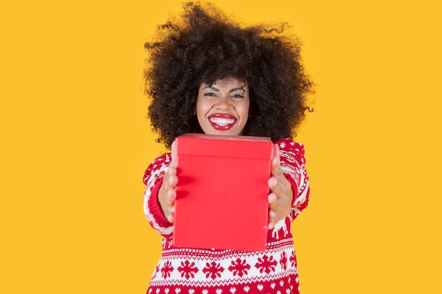 Ładna latynoska latynoska kobieta, boże narodzenie z prezentem w ręku, żółte tło