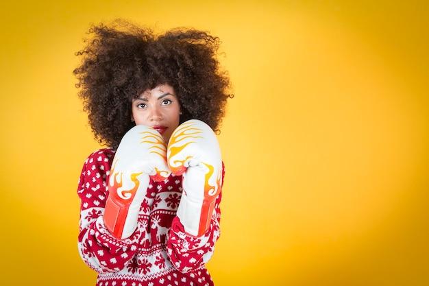 Ładna latynoska latynoska kobieta na boże narodzenie, na straży w rękawicach bokserskich. żółte tło