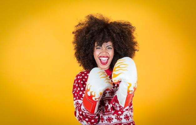 Ładna latynoska latynoska kobieta na boże narodzenie, w rękawicach bokserskich. żółte tło