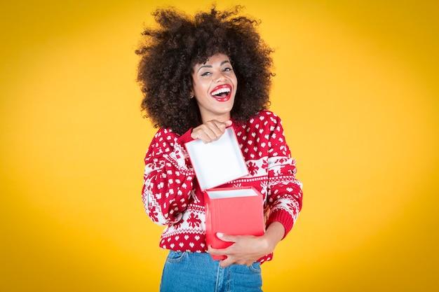 Ładna latynoska latynoska kobieta, otwierająca prezent świąteczny, szczęśliwe, żółte tło
