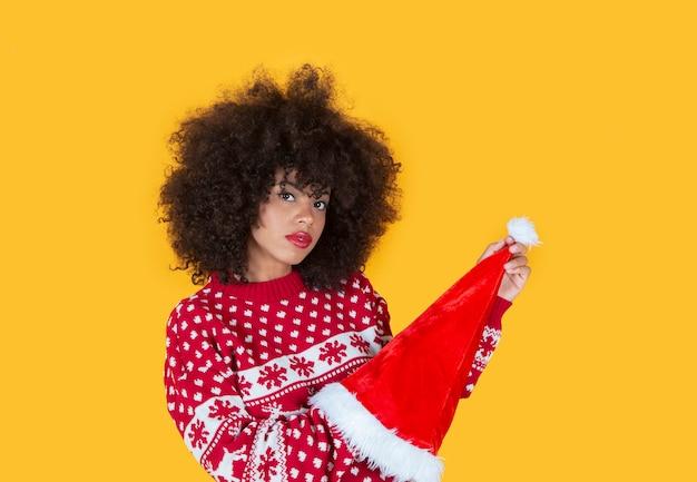Ładna latynoska latynoska kobieta, świąteczny kapelusz świętego mikołaja, żółte tło