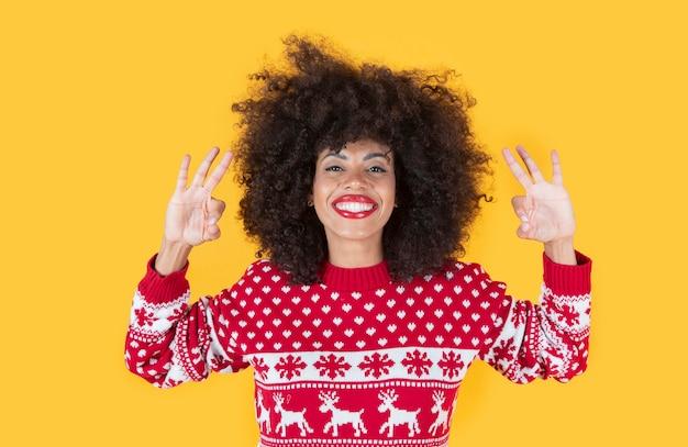 Ładna latynoska latynoska kobieta w świątecznych ubraniach i ok gestem