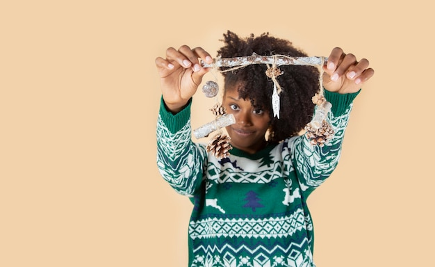 Ładna latynoska latynoska kobieta w zielonych świątecznych ubraniach, świątecznych dekoracjach, beżowym tle