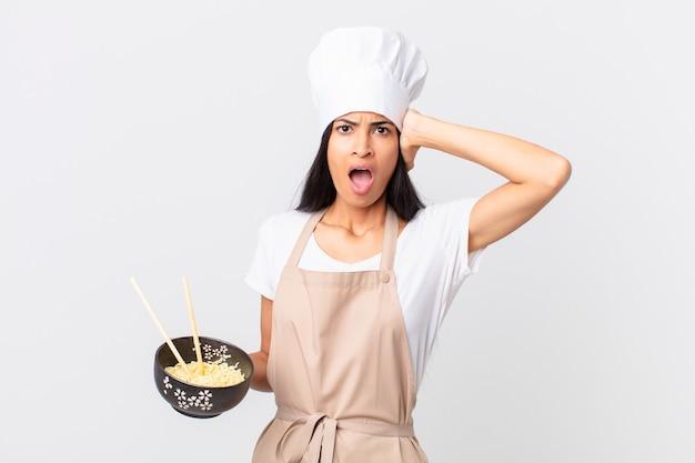 Ładna latynoska szefowa kuchni czuje się zestresowana, niespokojna lub przestraszona, z rękami na głowie i trzymająca miskę z makaronem