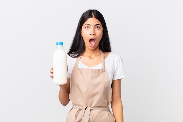Ładna latynoska szefowa kuchni, która wygląda na bardzo zszokowaną lub zaskoczoną i trzyma butelkę mleka