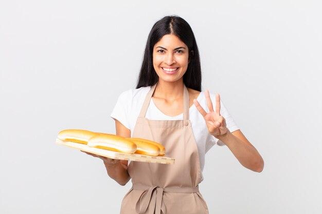 Ładna latynoska szefowa kuchni uśmiechnięta i wyglądająca przyjaźnie, pokazująca numer trzy i trzymająca tacę z bułeczkami