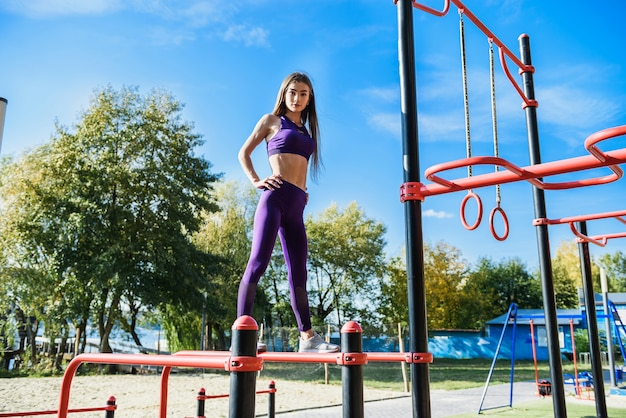 Ładna lekkoatletka kobieta robi poranne ćwiczenia na placu zabaw