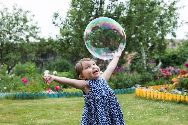 Ładna mała dziewczynka bawi się dużymi bąbelkami w parku.