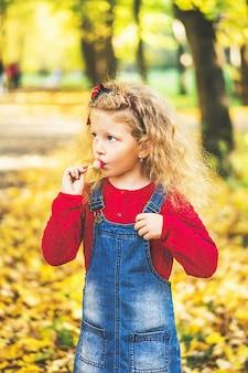 Ładna mała dziewczynka bawić się w parku, jesień czas.