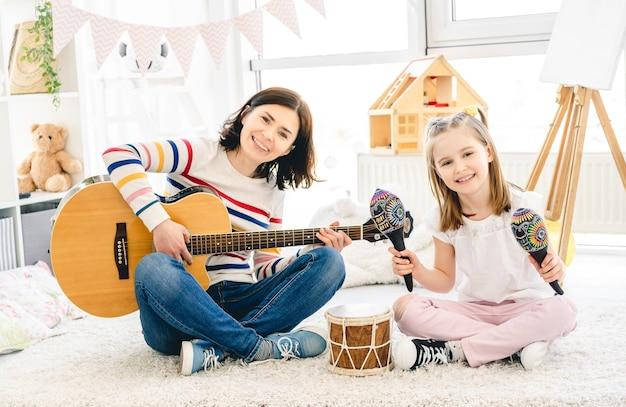 Ładna mała dziewczynka i matka grają na instrumentach muzycznych w pokoju dziecięcym?