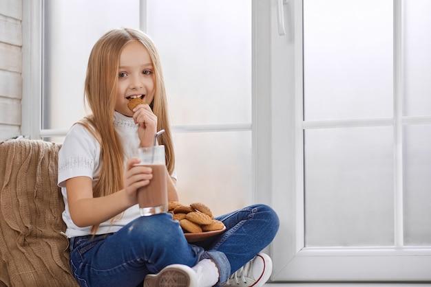 Ładna mała dziewczynka je ciastka z czekoladowym mlekiem