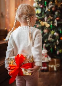 Ładna mała dziewczynka otwiera prezent gwiazdkowy.