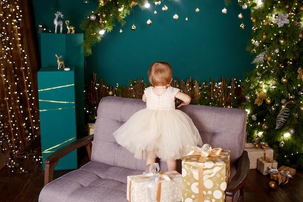 Ładna mała dziewczynka patrzeje na choince i światłach w biel sukni.