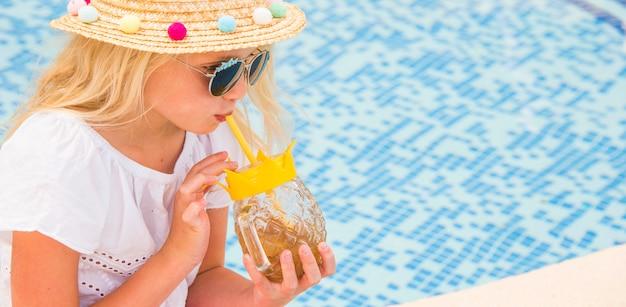 Ładna mała dziewczynka pije sok w pływackim basenie