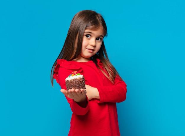 Ładna mała dziewczynka szczęśliwa ekspresja i trzymająca ciasto z filiżanką