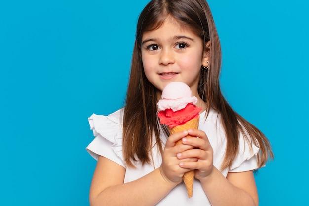 Ładna mała dziewczynka szczęśliwa ekspresja i trzymająca lody