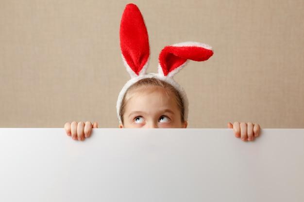Ładna mała dziewczynka szuka z powodu pustego sztandaru, w którym można wstawić dowolny tekst.