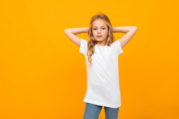 Ładna mała dziewczynka w białej koszulce gestykuluje i uśmiecha się na białej ścianie