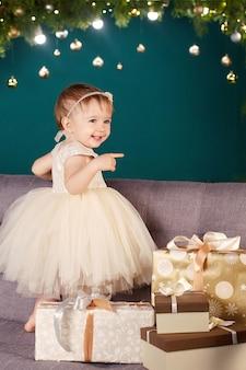 Ładna mała dziewczynka w biel sukni bawić się i jest szczęśliwy o choince i światłach.