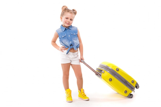 Ładna mała dziewczynka w niebieskiej koszuli, białych spodenkach i okularach przeciwsłonecznych trzyma żółtą walizkę przy uchwycie