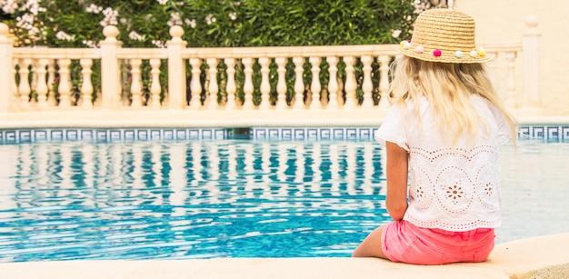 Ładna mała dziewczynka w pływackim basenie, wakacje.