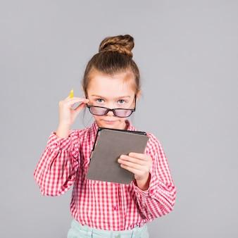Ładna mała dziewczynka w szkłach używać pastylkę