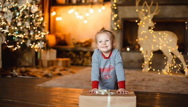 Ładna mała dziewczynka w tradycyjnej piżamie otrzymała świąteczny prezent w domu