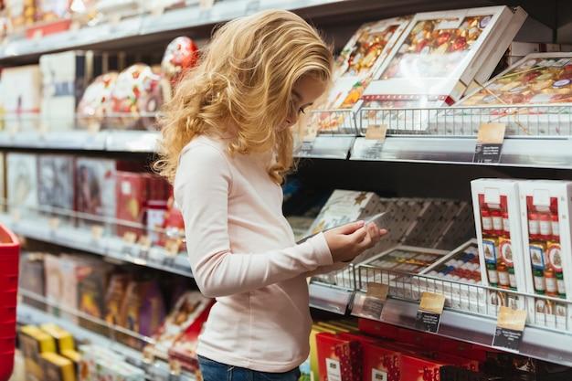Ładna mała dziewczynka wybiera cukierek przy supermarketem