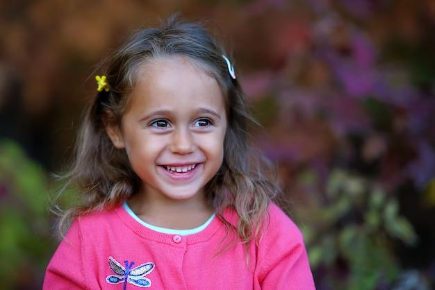Ładna mała dziewczynka z dużymi oczu ono uśmiecha się
