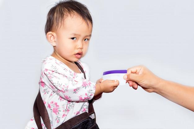 Ładna mała dziewczynka z torba mienia kredytową kartą dla robić zakupy na białym tle