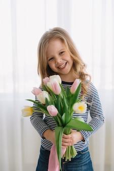 Ładna mała dziewczynka z wiązką tulipany na szczęśliwym matka dniu. robi prezent dla swojej mamy.