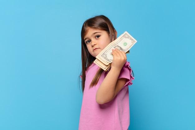Ładna mała dziewczynka zły wyraz twarzy i banknoty dolarowe