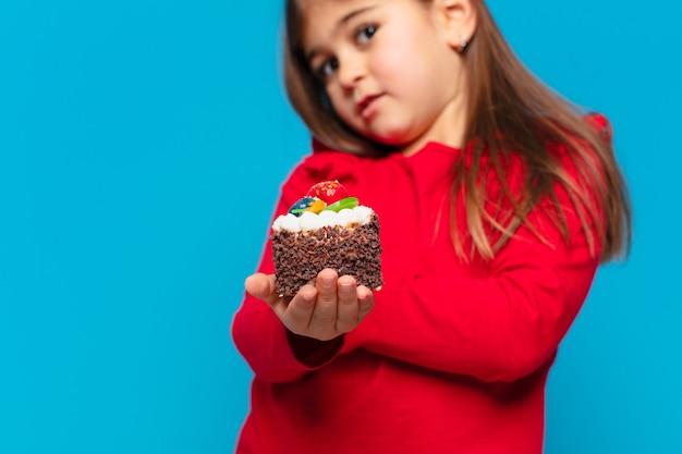 Ładna mała dziewczynka zły wyraz twarzy i trzymająca ciasto z filiżanką